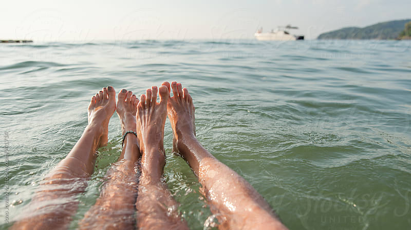 Couple's feet in ocean - floating together by Jovo Jovanovic for Stocksy United