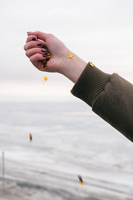 Girl's hand with falling golden stars by Danil Nevsky for Stocksy United