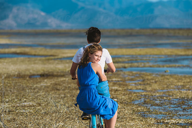 Couple Riding Bike On Beach by Alexander Grabchilev for Stocksy United