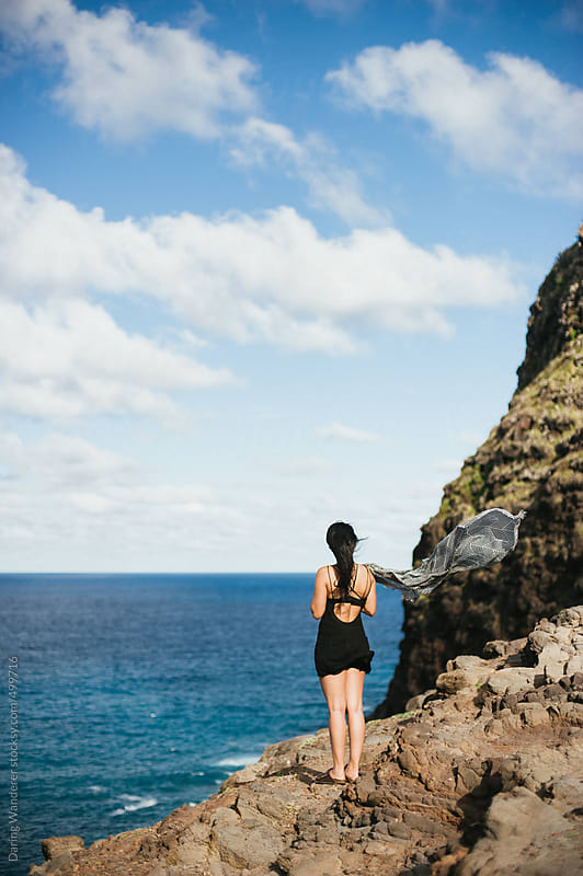 Woman standing on edge of rock overlooking ocean in Hawaii by Daring Wanderer for Stocksy United