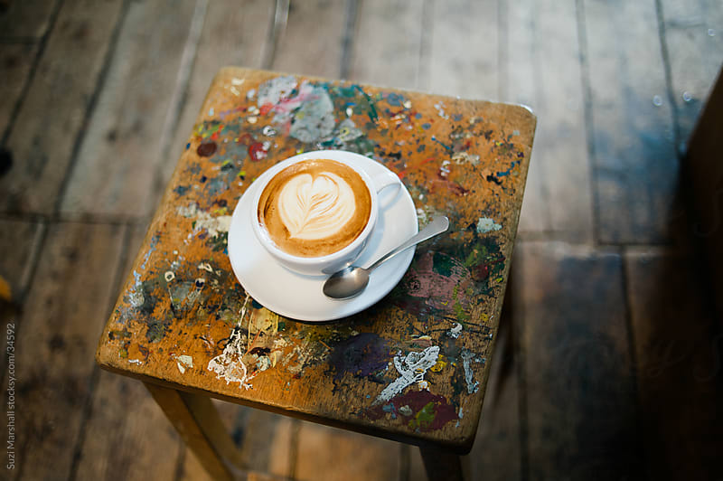 Cup of coffee with heart latte art on a table by Suzi Marshall for Stocksy United