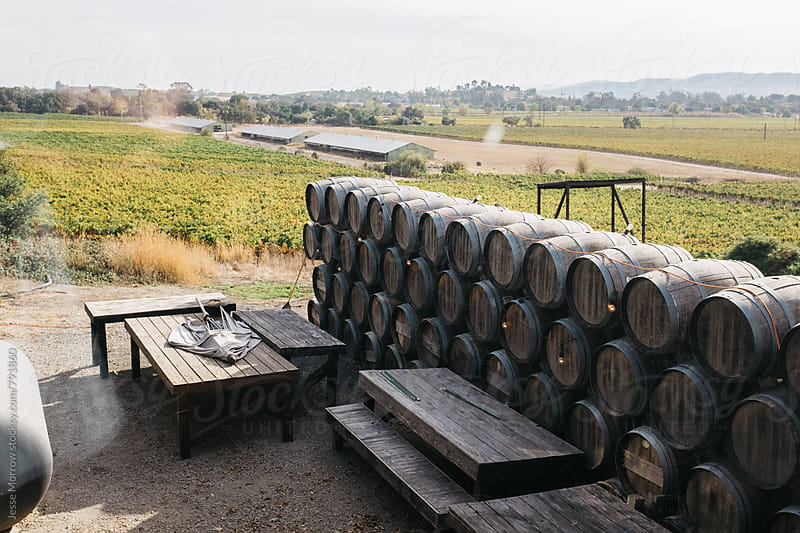 row of wine barrels stack on each other outdoors by Jesse Morrow for Stocksy United