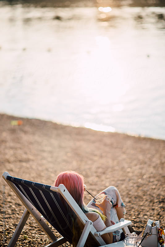 Young woman sitting in a beach chair by Boris Jovanovic for Stocksy United