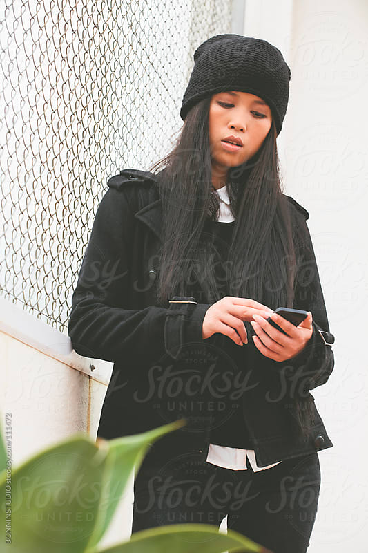 Young chinese woman standing on a terrace with mobile phone. by BONNINSTUDIO for Stocksy United