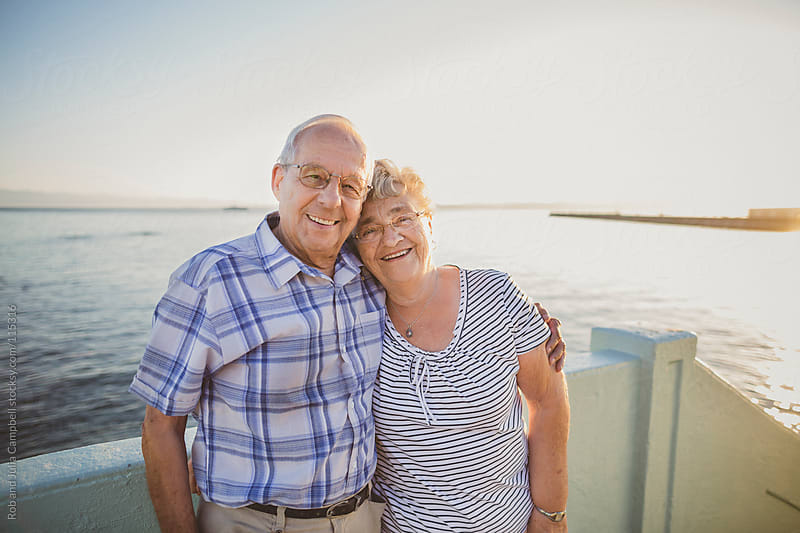 Elderly couple smiling by the sea by Rob and Julia Campbell for Stocksy United