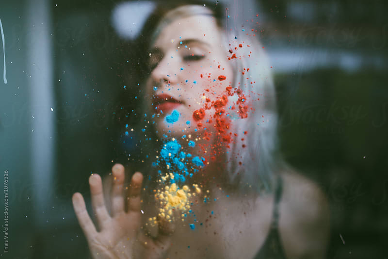 woman behind a pigmented window by Thais Ramos Varela for Stocksy United