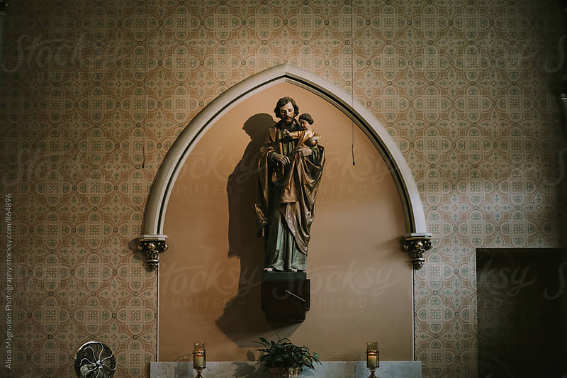 Interior wall of Ornate Catholic Church Sanctuary with Statue by Alicia Magnuson Photography for Stocksy United