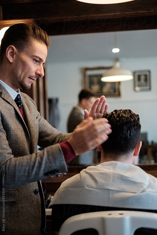 A gentleman barber readies a client's hair for a proper cut. by Riley J.B. for Stocksy United
