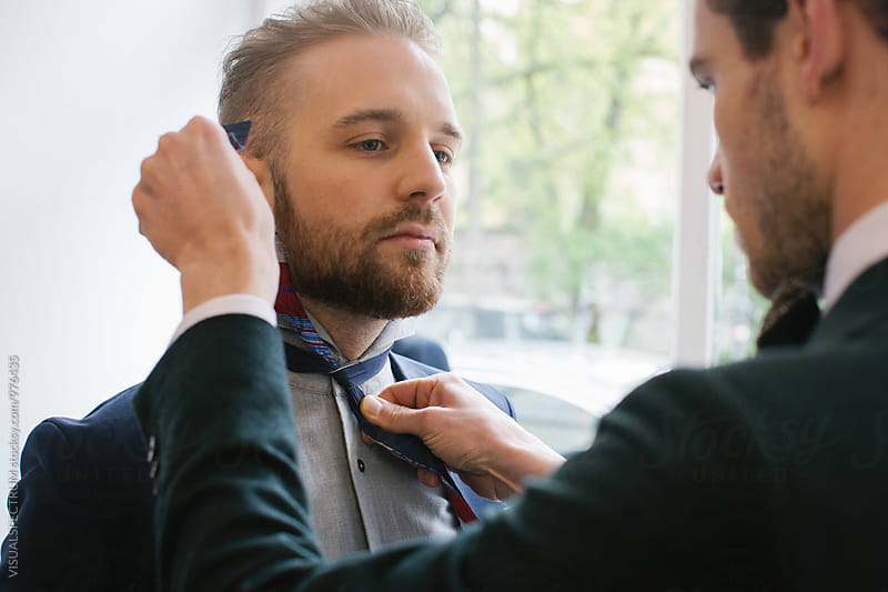 Men's Fashion - Close Up of Man Helping Young Male Friend to Tie Bow Tie by VISUALSPECTRUM for Stocksy United