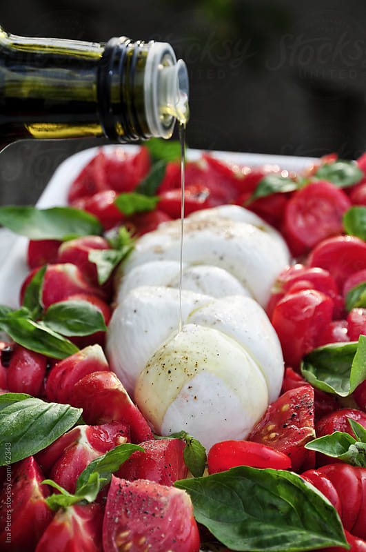 Food: Bulls heart tomatos Caprese Salad by Ina Peters for Stocksy United
