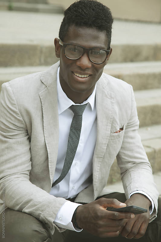Smiling african young businessman sending a message on smartphone by BONNINSTUDIO for Stocksy United