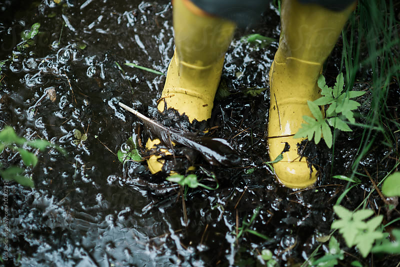 yellow rain boots in mud by Léa Jones for Stocksy United