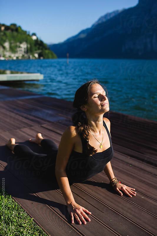 Woman doing yoga pose: Urdhva Mukha Svanasana by michela ravasio for Stocksy United