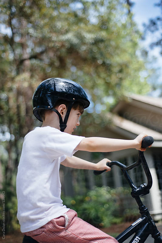 Boy rides a bike while wearing a helmet by Cara Dolan for Stocksy United