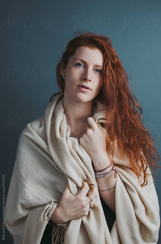 Portrait of young red head woman with blanket on solid background by Rob and Julia Campbell for Stocksy United
