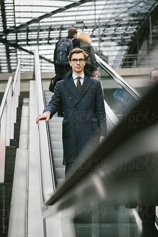 Businessman On Escalator by VegterFoto for Stocksy United