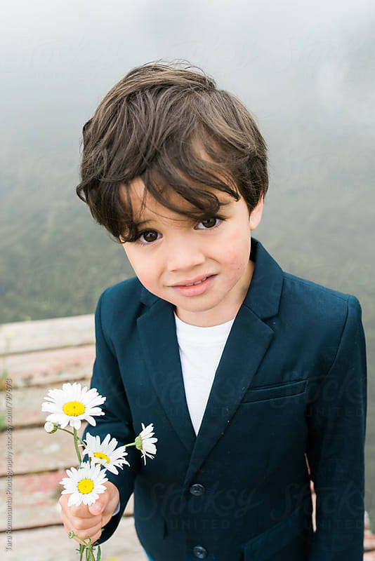 handsome little boy with flowers in his hand by Tara Romasanta for Stocksy United