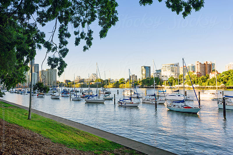 Brisbane River with boats moored in the foreground, looking to the city and Storey Bridge by Gillian Vann for Stocksy United