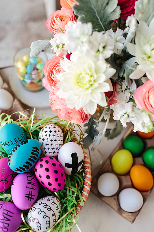 Hand drawn & colored easter eggs next to fresh cut flowers by Kristen Curette Hines for Stocksy United