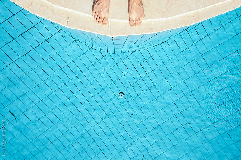 Feet of a man standing on the edge of pool ready to jump into the water by Ilya for Stocksy United