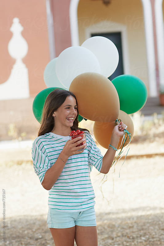 Beautiful young girl with balloons and tomatoes for a celebration by Miquel Llonch for Stocksy United