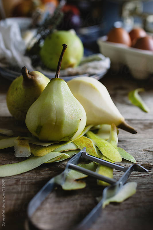 Peeling pears for use in a dessert.  by Darren Muir for Stocksy United