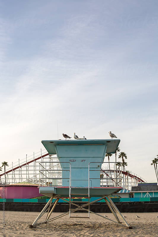 Lifeguard station on beach with amusement park in background by Amy Covington for Stocksy United