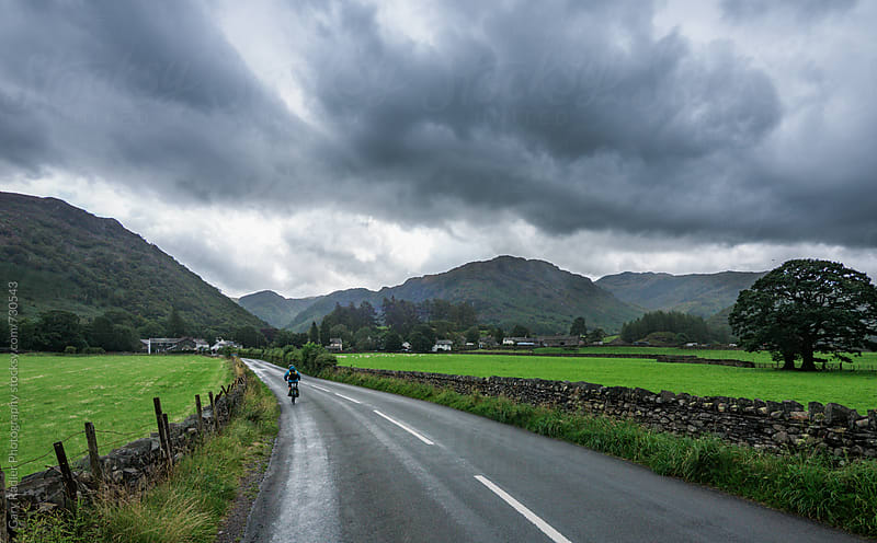 Cyclist nearing Borrowdale, Lakes District, England by Gary Radler Photography for Stocksy United