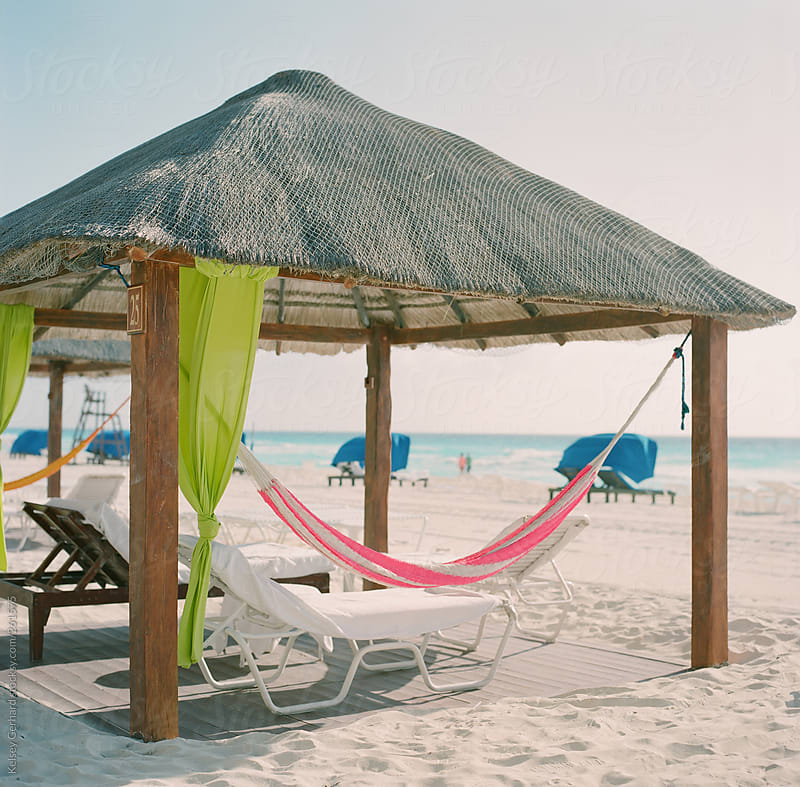 A hammock hangs in a Mexican cabana on the beach shot on film. by Kelsey Gerhard for Stocksy United