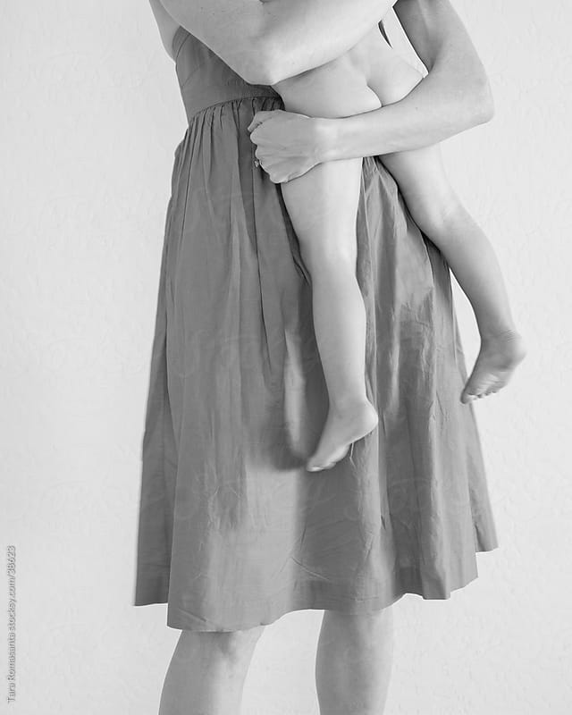 a mom holds a bare bottomed toddler in her arms by Tara Romasanta for Stocksy United