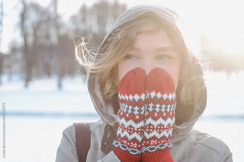 Woman hiding her face with her hands in mittens by Lyuba Burakova for Stocksy United