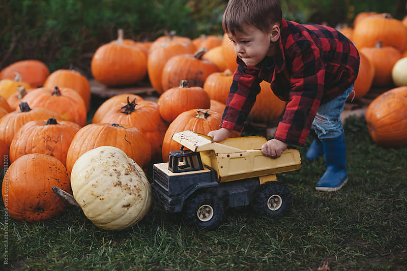 Cute little boy in plaid jacket pushing dumptruck at pumpkin farm by Rob and Julia Campbell for Stocksy United