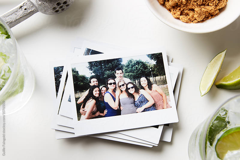 Pile of printed photos with friends in garden posing at camera by Guille Faingold for Stocksy United