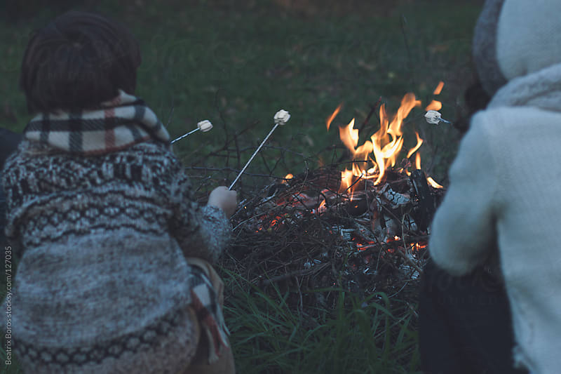 Marshmallow roasting at the fire outdoors by Beatrix Boros for Stocksy United