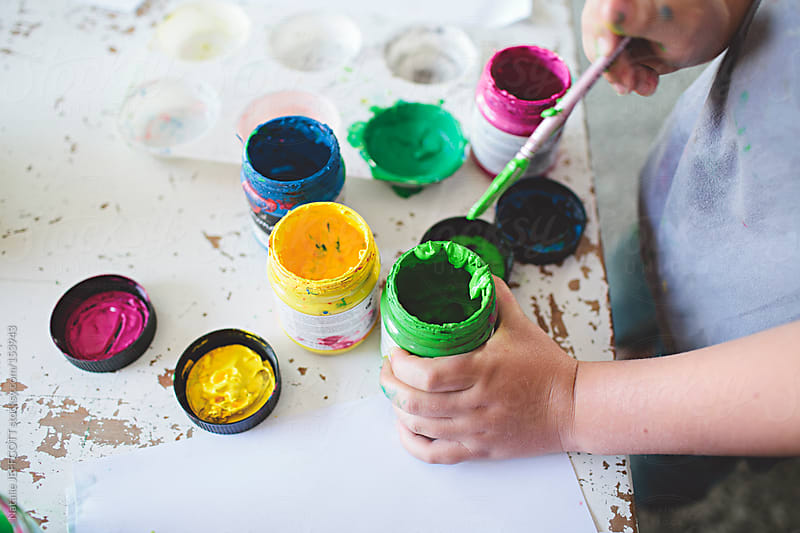 close up of young boy mixing paint to create an artwork by Natalie JEFFCOTT for Stocksy United