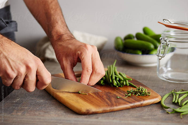 Man's hands cutting green beans by Martí Sans for Stocksy United