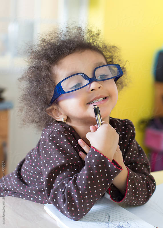 Portrait of a toddler wearing blue glasses sitting studiously as she scribbles and writes on a notepad by anya brewley schultheiss for Stocksy United
