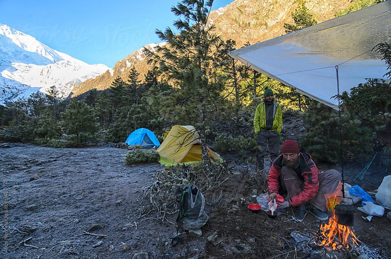 Trekkers making breakfast on open fire in the tent camp in the mountains on early morning by Alice Nerr for Stocksy United