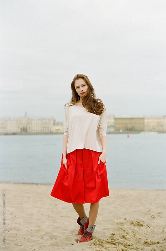 Young woman standing at the Neva river front  by Lyuba Burakova for Stocksy United