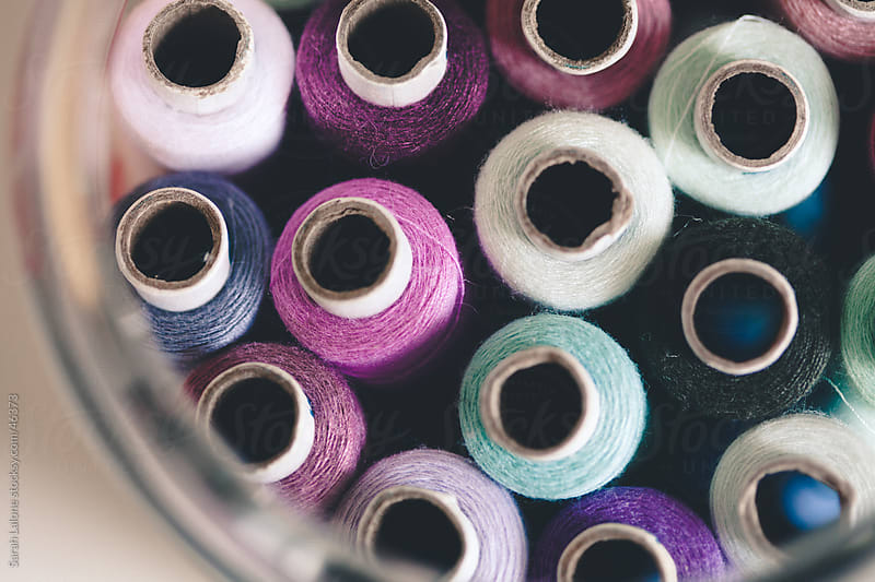 Purple and green thread spools in a jar by Sarah Lalone for Stocksy United