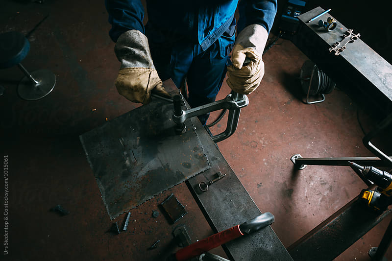 Metal worker fixing iron plate with bar clamp  by Urs Siedentop & Co for Stocksy United