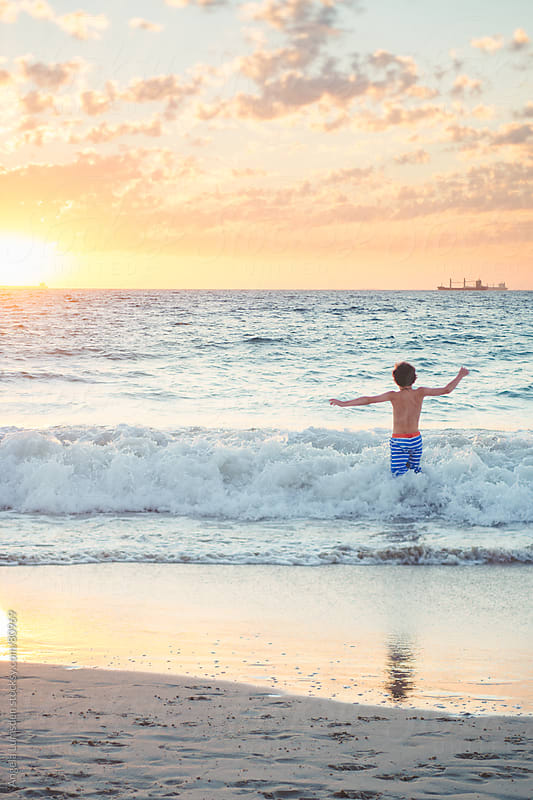 Boy swimming at the beach at sunset by Angela Lumsden for Stocksy United