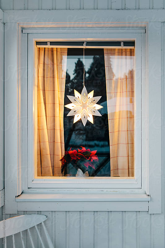 Christmas star ornament  hanging in window by Stephen Morris for Stocksy United