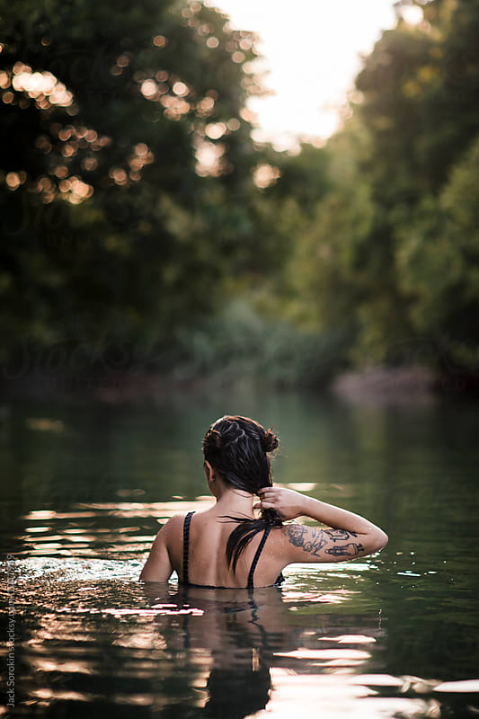 Young Woman Swimming In Creek And Wringing Out Her Hair by Jack Sorokin for Stocksy United