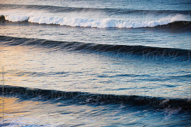 Breaking waves in the blue ocean sea with the sunset reflecting on the water by Alejandro Moreno de Carlos for Stocksy United