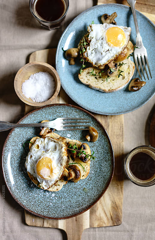 Crostini with crispy fried egg and garlic mushrooms with herbs. by Darren Muir for Stocksy United