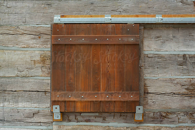 Barn door style window shutter on a log cabin by David Smart for Stocksy United