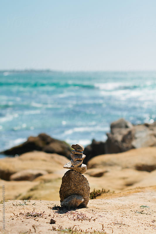 a cairn on the coast by Jess Lewis for Stocksy United