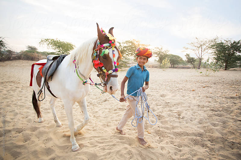 Young boy training horse in Rajasthan Desert. India. by Hugh Sitton for Stocksy United