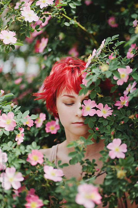 Portrait of redhair female hide behind a flowering wild rose  by Sergey Filimonov for Stocksy United